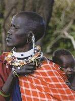 Description: Maasai woman carrying her baby in traditional clothing and jewelry in the Serengeti...